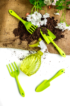 pitchfork: green garden tools and ground for planting flowers on white table background top view