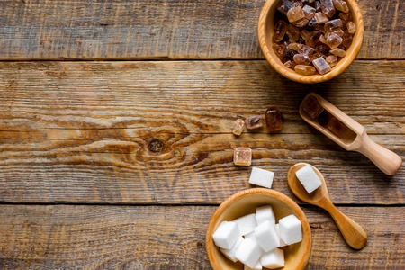 variety of sugar in bowls on wooden table background top view space for text