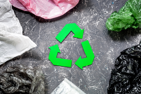Paper recycle sign with plastic garbage on grey table background top view Stock Photo