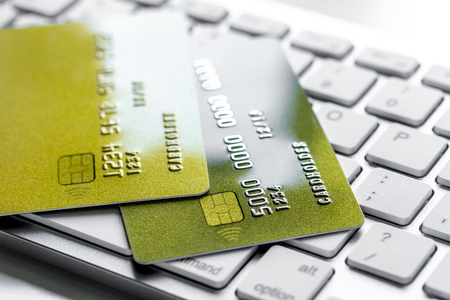 Payment composition with business credit cards on keyboard at office work place white background close up