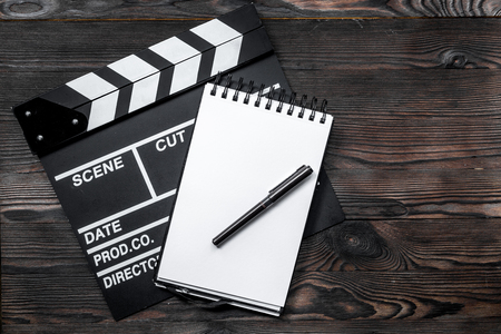 Work table of producer. Movie clapperboard and notebook on wooden table background top view copyspace