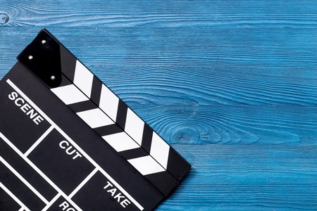 Movie clapperboard on blue wooden table background top view copyspace