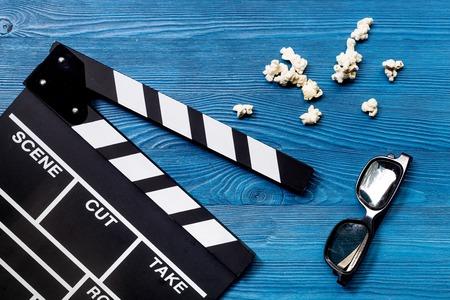 Je regarde le film Clap de cinéma, lunettes de soleil et maïs soufflé sur la vue de dessus du fond de table en bois bleu Banque d'images - 80632946