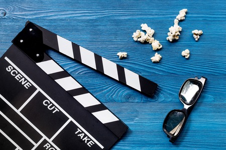 Watching the film. Movie clapperboard, sunglasses and popcorn on blue wooden table background top view
