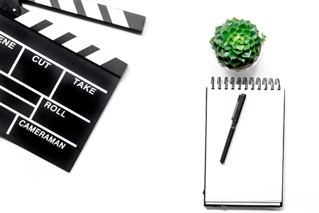 screenwriter: Work table of producer. Movie clapperboard and notebook on white background top view Stock Photo