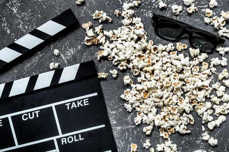 Watching the film. Movie clapperboard, sunglasses and popcorn on grey stone table background top view Stock Photo