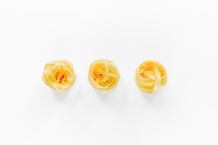 Italian pasta fettuccine nest on white background close up top view copyspace