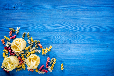 Italian pasta fettuccine and fusilli on blue wooden desk background top view copyspace