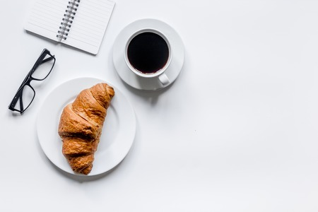 Businessman morning with notebook, cup of coffee and croissant on wooden table background top view mockup Фото со стока