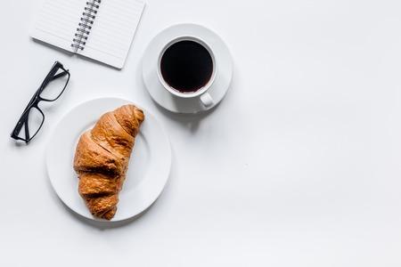 Geschäftsmannmorgen mit Notizbuch, Tasse Kaffee und Hörnchen auf Draufsichtmodell des Holztischhintergrundes