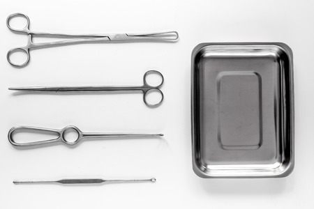 Surgical instruments and tools including scalpels, forceps and tweezers on white table top view mock up