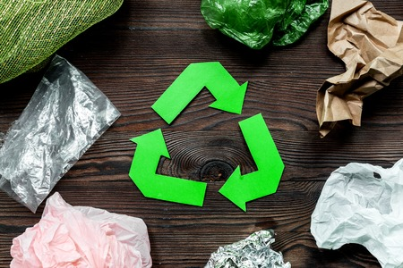 Paper recycle sign with plastic garbage on wooden background top view Stock Photo