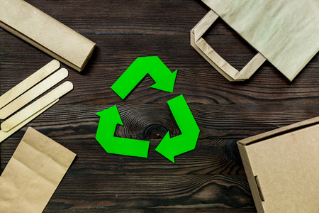 Paper recycle sign with paper and carton garbage on wooden background top view