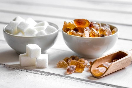 lumps of white and brown sugar on white wooden table background Stock Photo