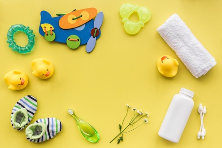 bath cosmetic set for kids, towel and toys yellow background top view space for text