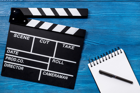 Work table of producer. Movie clapperboard and notebook on blue wooden table background top view