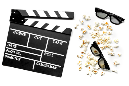 Watching the film. Movie clapperboard, sunglasses and popcorn on white background top view Banco de Imagens