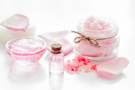 cosmetic set with rose blossom and body cream on white desk background