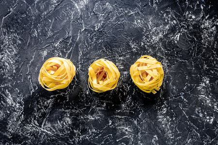 Italian pasta fettuccine nest on grey stone table top view copyspace