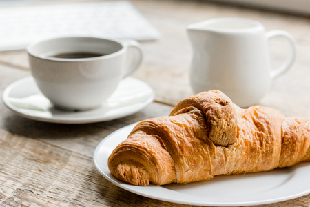 Business breakfast in office with coffee, milk and croissant on wooden table background