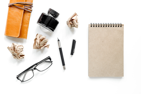 Writer acsessories. Glasses pen and notebook on white background top view mockup