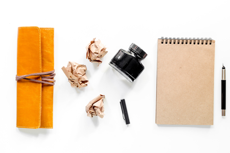 Writer workplace with vintage notebook and crumpled paper on white background top view mockup
