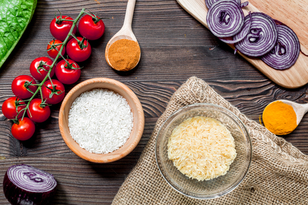rice, spices and vegetables for paella on wooden desk background top view Stock Photo