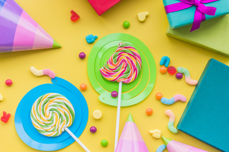 Lollipops and party hats for happy birthday on yellow background top view Stock Photo