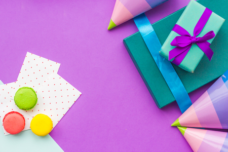 Birthday wrapped gifts and party hats on purple background top view copyspace Stock Photo