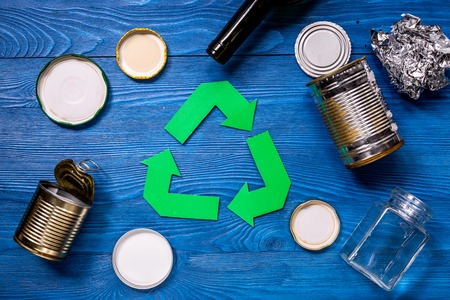 Paper recycle sign with steel garbage on blue table background top view Stock Photo