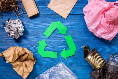 Paper recycle sign with plastic garbage on blue wooden background top view Stock Photo