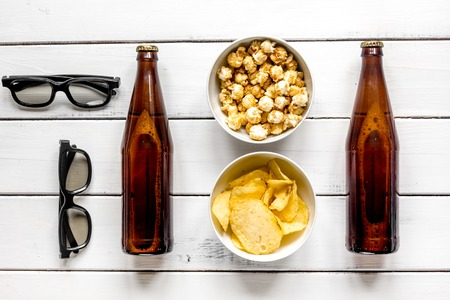 glasses, snacks, beer for whatchig film on white wooden background top view Stock Photo