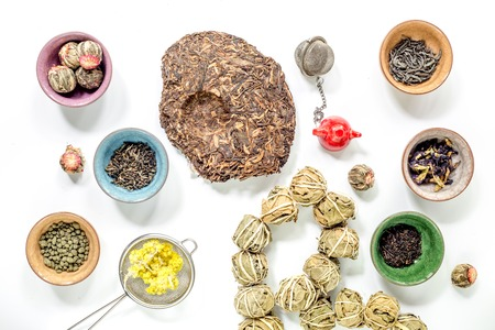 Different kinds of herbal tea on white table background top view