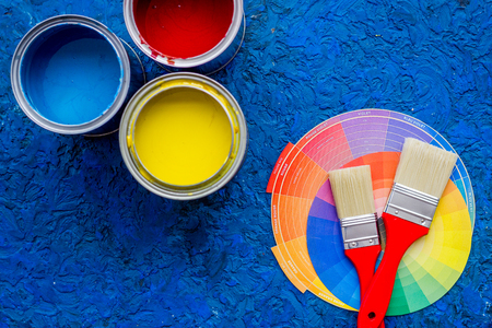Colorful paints and brushes on blue wooden desk background top view copyspace