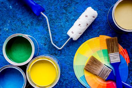 カラフルな塗料と背景の青い木製机の上でブラシを表示します。 写真素材