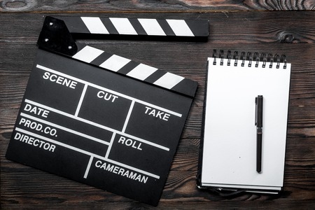 Work table of producer. Movie clapperboard and notebook on wooden table background top view Stock Photo