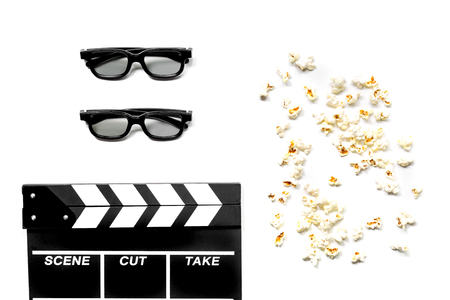 Watching the film. Movie clapperboard, sunglasses and popcorn on white background top view Imagens - 80787617