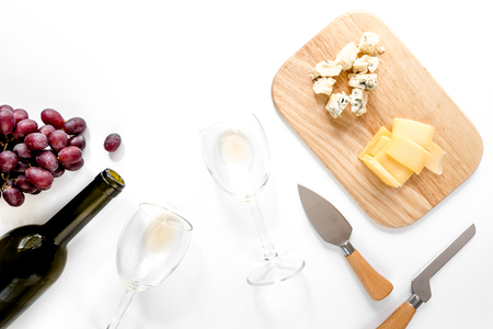 Set for drinking wine with cheese and red grape on white background copyspace top view