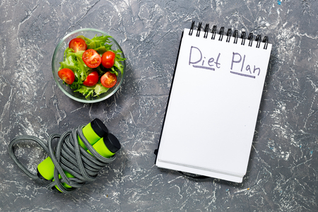 Notebook for diet plan, salad with fresh products and jump rope on stone table top view mock up