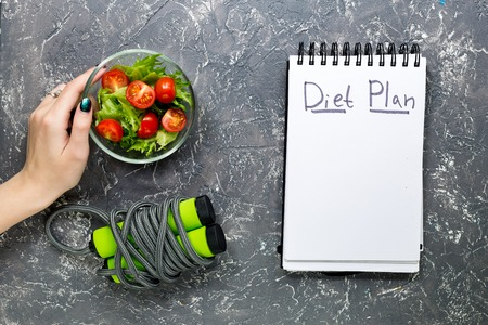 Notebook for diet plan, hand is holding salad with fresh products and jump rope on stone table top view mock up