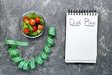 Notebook for diet plan, salad and measuring tape on grey stone table top view mock up