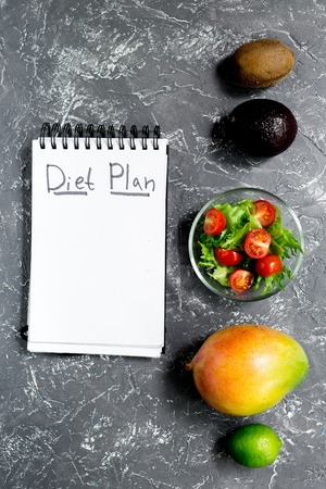 Slimming. Notebook for diet plan, fruits salad on grey stone table top view mock up