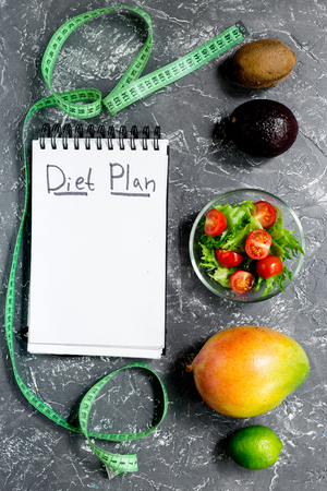 Slimming. Notebook for diet plan, fruits salad and measuring tape on grey stone table top view mock up