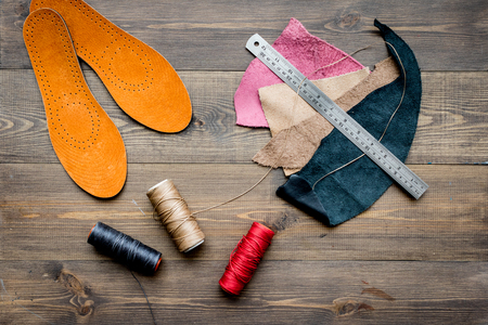 Working place of shoemaker. Skin on brown wooden desk background top view Stock Photo