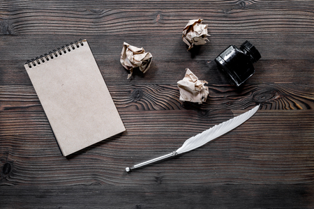 Writer concept. Feather pen, ink, notebook and crumpled paper on wooden table background top view mockup