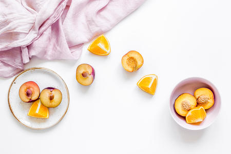 woman summer breackfast with orange and peach fruits and pink fabric on white desk background flat lay