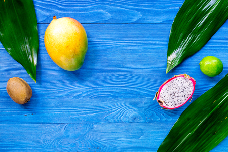 Exotic fruit meal. Dragonfruit, mango, kiwi, lime on blue wooden table background top view copyspace Stock Photo