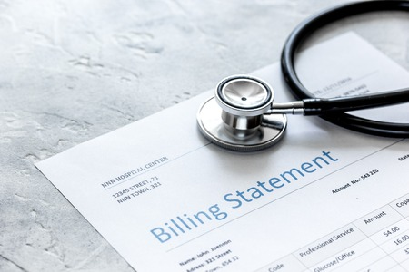 health care costs with billing statement, stethoscope on stone table Foto de archivo