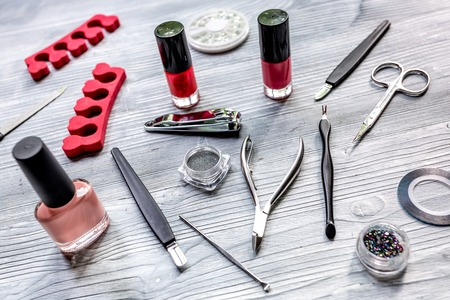salon and spa: manicure preparation set with nail polish bottles on gray background Stock Photo