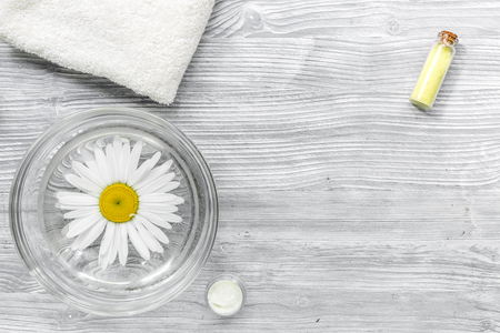 hands care set for manicure with chamomile on gray wooden background top view space for text. Stock Photo